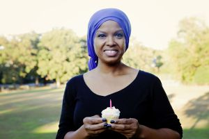A woman with cancer wearing a scarf on her head and holding a cupcake with a pink candle