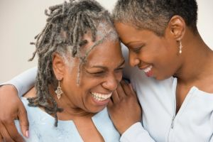 An adult daughter wrapping her arms around her smiling mom