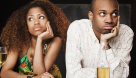 Couple sitting at bar and looking irritated