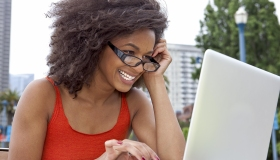 Young woman smiling working on a laptop computer