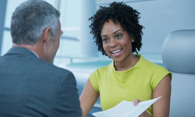 Black woman handing over resume