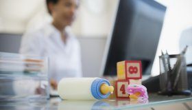 Baby bottle and blocks on African American woman's desk