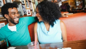 Smiling couple sitting in diner booth