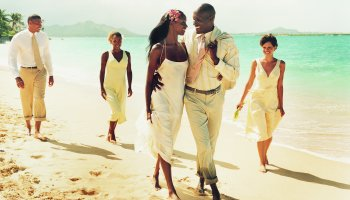 Newlywed Couple Walk Face-to-Face on a Beach, Accompanied by Bridesmaids and Best Man