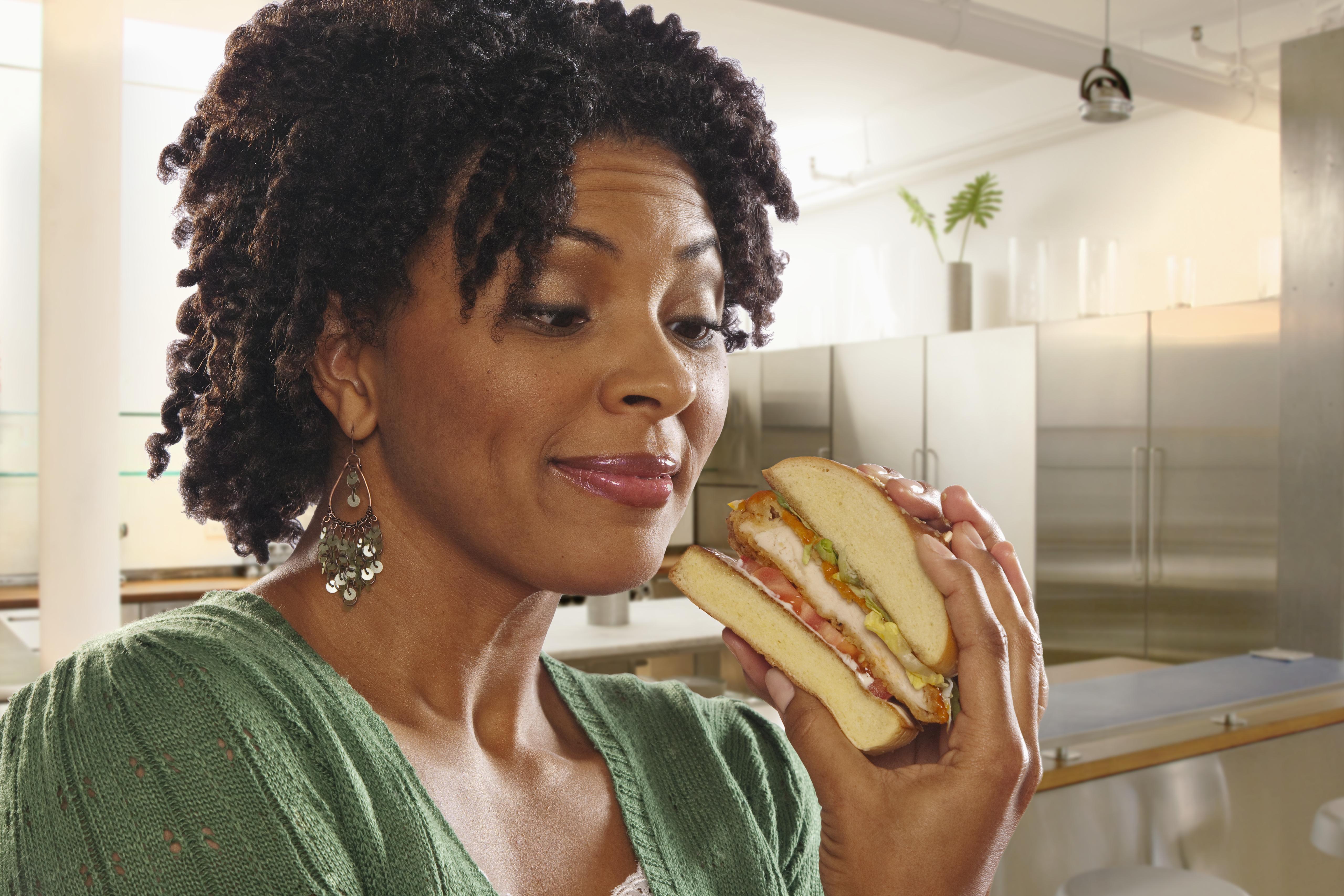 African American woman eating sandwich