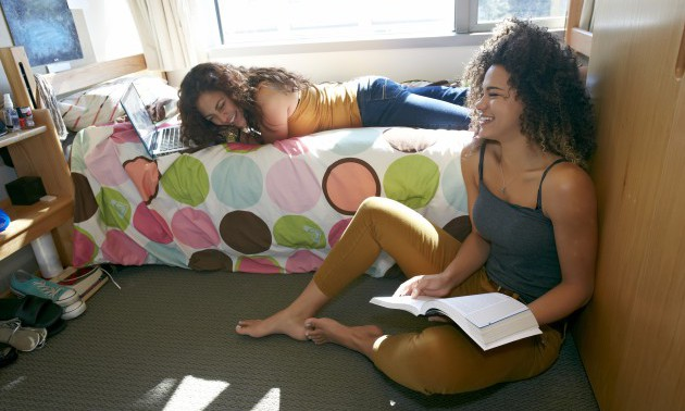 Mixed race college students relaxing in dorm
