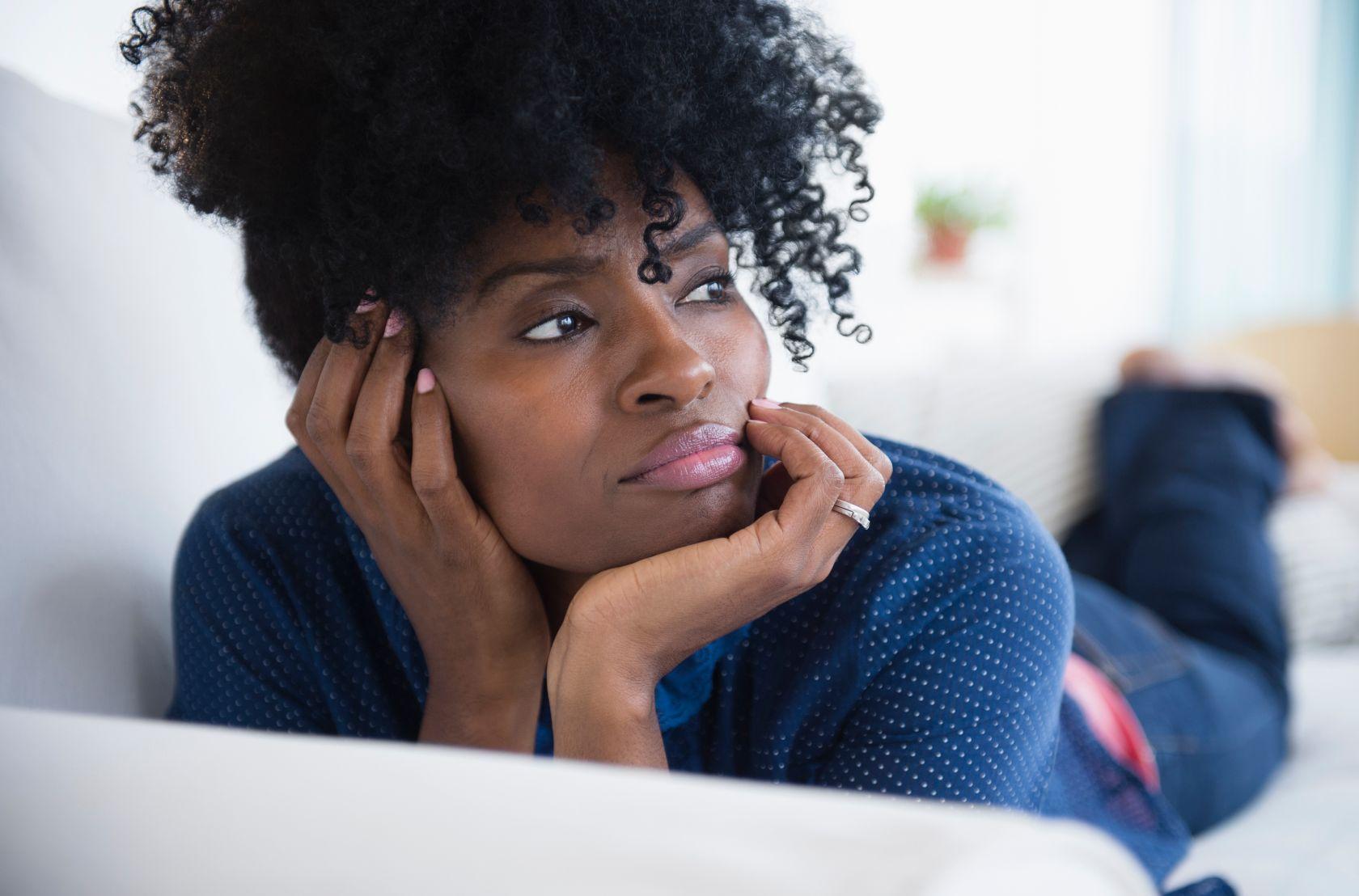 Black woman laying on sofa