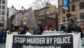 Members of 'Stop Mass Incarceration' carry banner 'Stop...