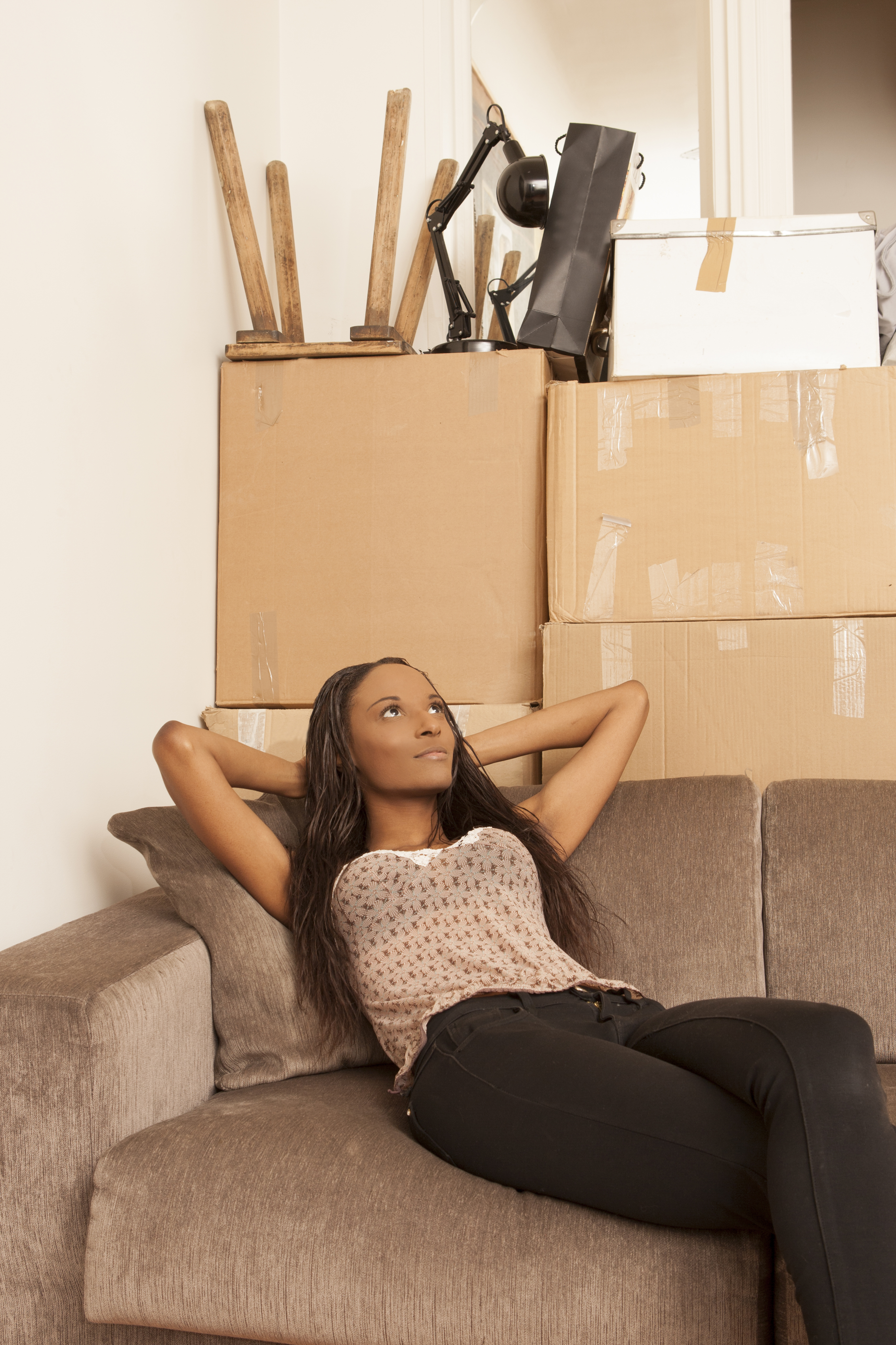 Woman sitting in flat surrounded by boxes