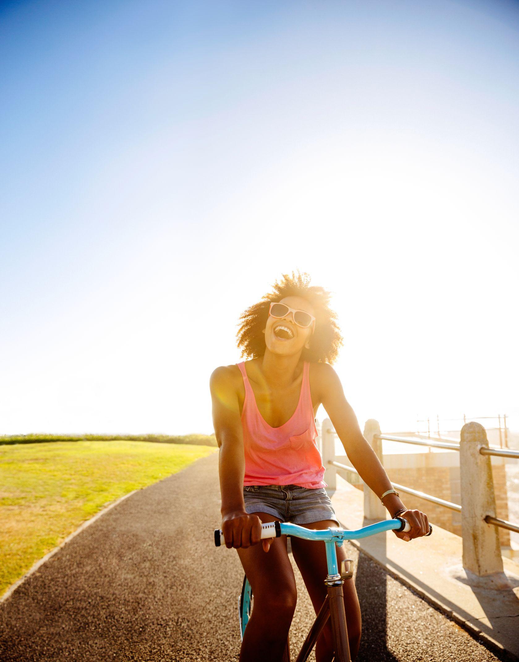 teenage girl riding her bike near beach
