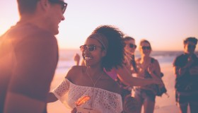 Afro girl dancing with her boyfriend at a sunset beachparty