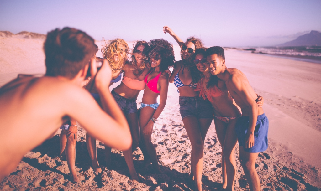 Guy taking a picture of group of friends on beach