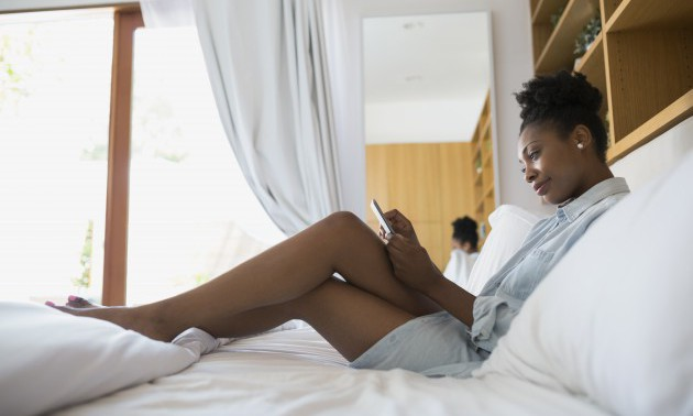 Woman using digital tablet in bed