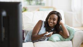 Black woman watching television on sofa