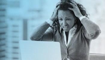 Black woman upset looking at computer