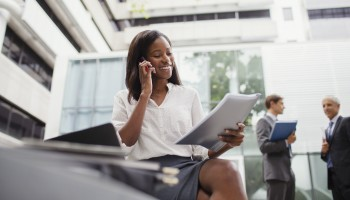 Businesswoman talking on cell phone looking at documents