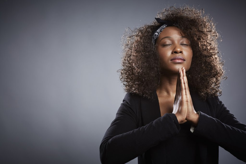 Studio portrait of young businesswoman praying