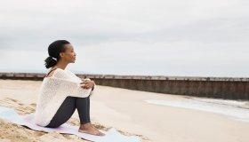 Serene woman sitting beach blanket looking at view