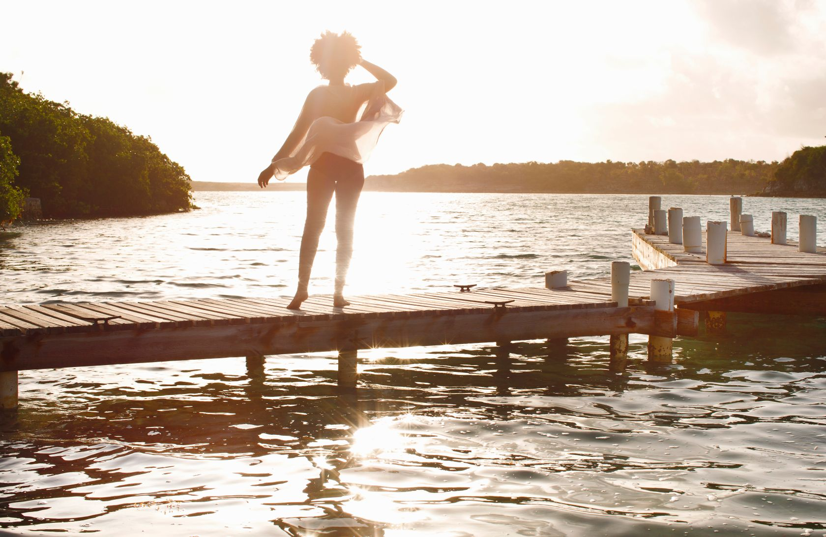Young woman looking out to sea from boat dock.