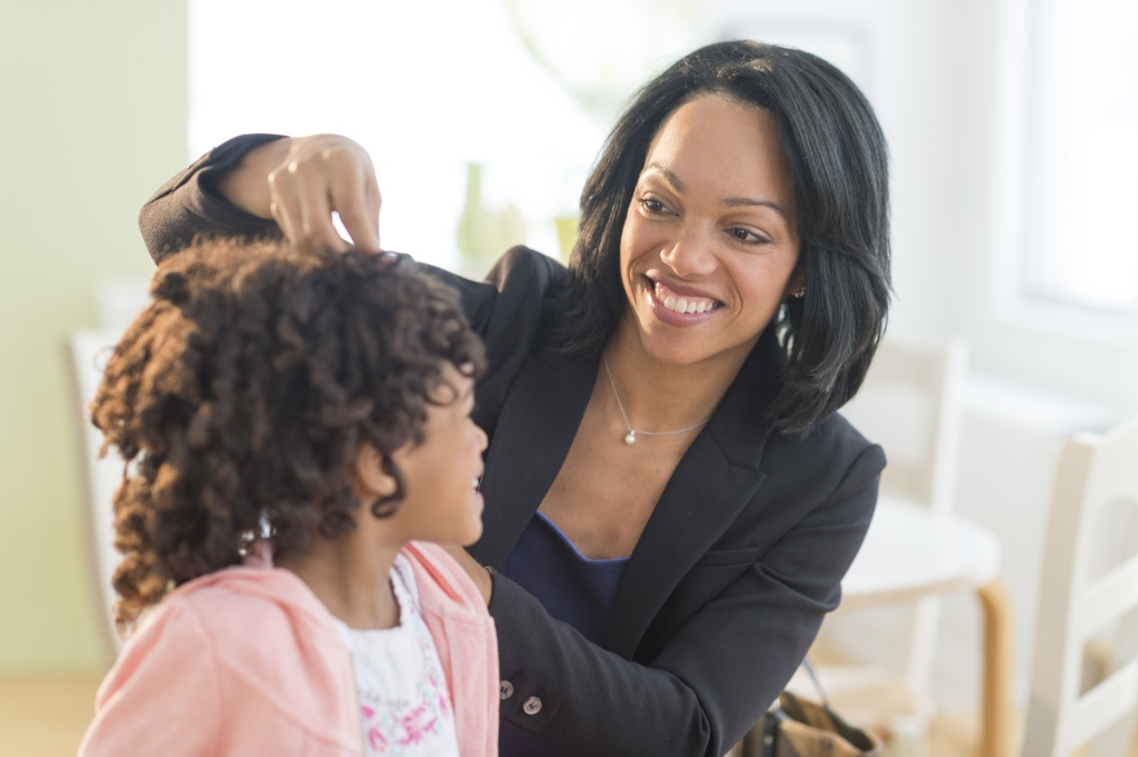 African American mother fixing daughter's hair