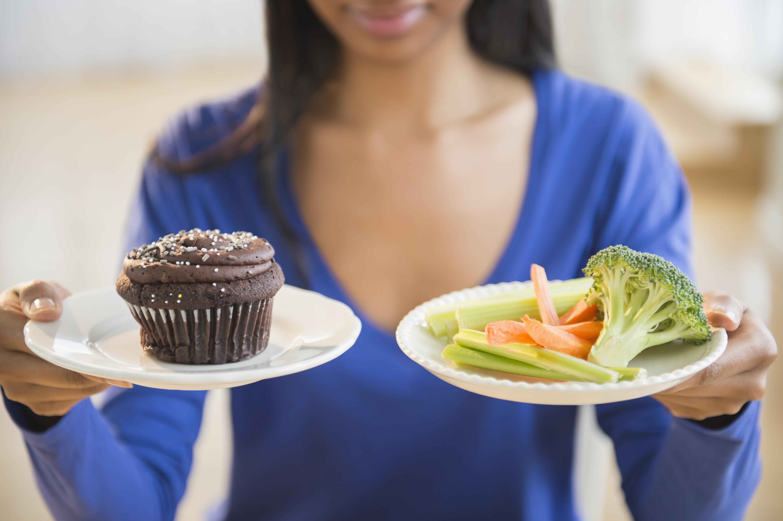 woman holding cupcake and veggies
