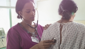 Nurse listening to heartbeat of patient in hospital room