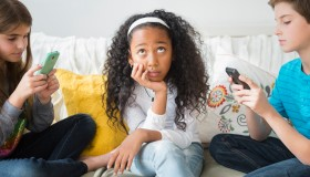 Annoyed girl ignoring friends using cell phones on sofa