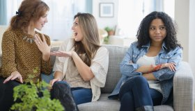 Chatting women ignoring upset friend on sofa