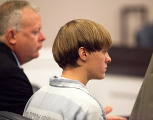 Dylann Roof (R), the 21-year-old man charged with murdering nine worshippers at a historic black church in Charleston last month, is helped to his chair by chief public defender Ashley Pennington during a hearing at the Judicial Center in Charleston