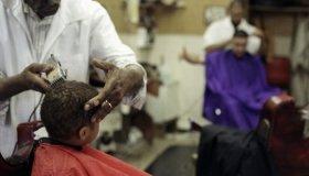 Boy getting hair cut in barber shop