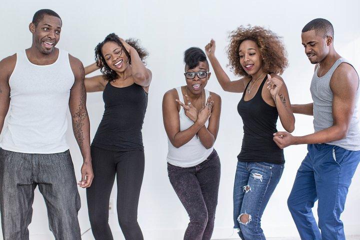 Studio portrait of five adult friends dancing