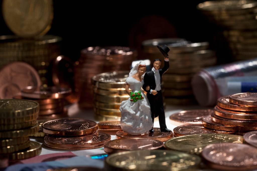 Miniature wedding couple figurines amidst stacks of European Union coins