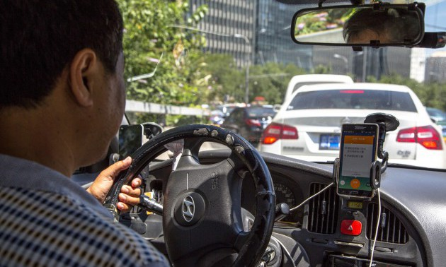 A taxi driver is using Didi Dacha App while driving on the...
