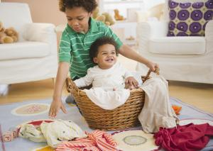 Black boy putting sister in laundry basket