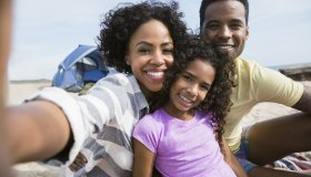 Portrait smiling family on beach