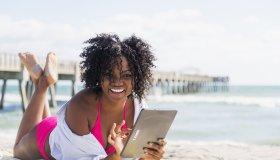 African American woman using digital tablet on beach