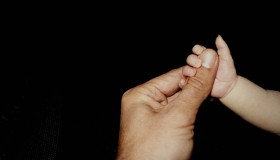 Cropped Baby Hand Holding Thumb Of Father Against Black Background