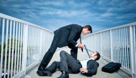 Caucasian businessmen fighting on elevated walkway
