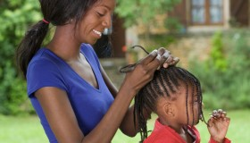 African mother braiding daughter's hair
