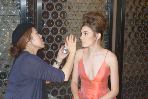 Makeup artist backstage placing final touches on model in organza A-line dress.