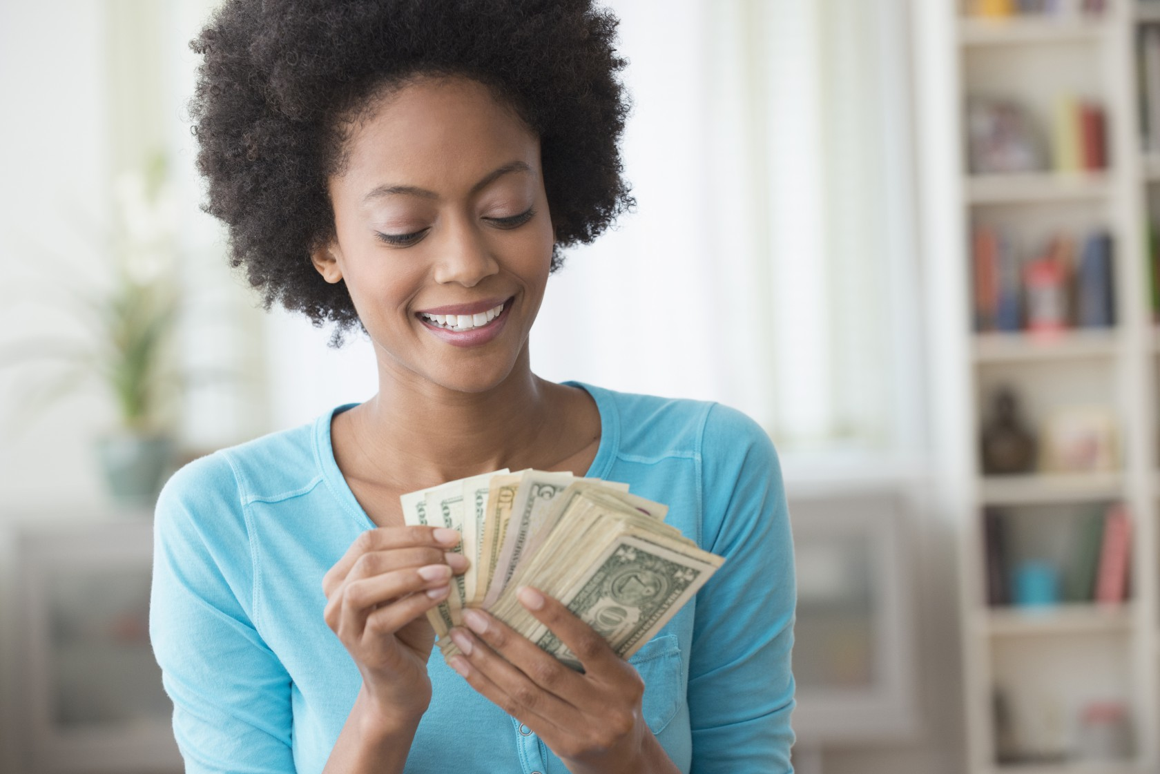 African American woman counting money in living room