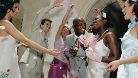 Guests throwing confetti over newlywed couple