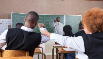 A teacher scolding students for passing notes in the classroom, Cape Town, South Africa