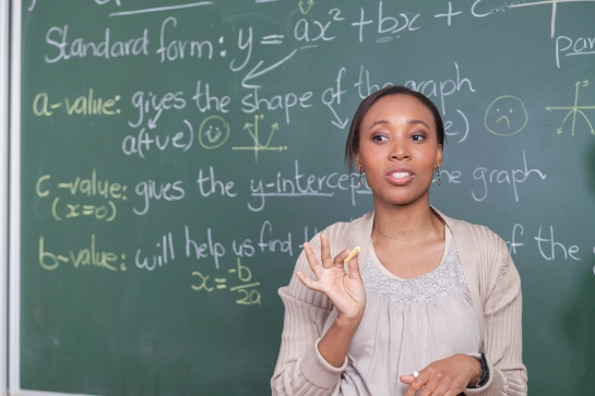 Head and shoulder of female teacher with mathematics equations on the chalkboard, Cape Town, South Africa