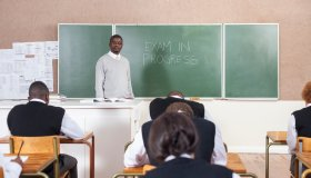 A Teacher standing by the chalk board while students write an exam. Cape Town, South Africa