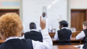 Waist up shot of African male teacher leading biology class, out of focus, students foregrounded with hands up, Cape Town, South Africa