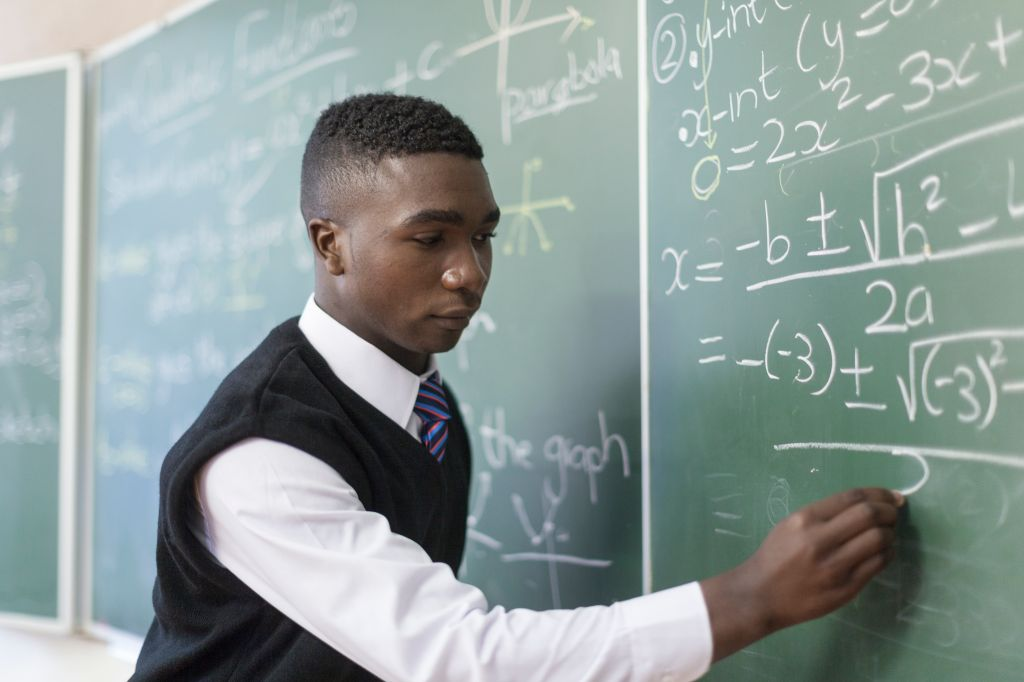 Medium shot of African male student writing on chalkboard, Cape Town, South Africa