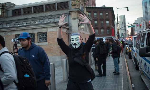 A participant in the rally wearing a Guy Fawkes mask raises...