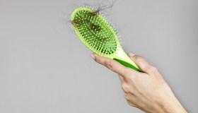 Woman losing hair on hairbrush