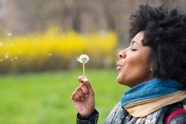 Black woman blowing dandelion seeds in park